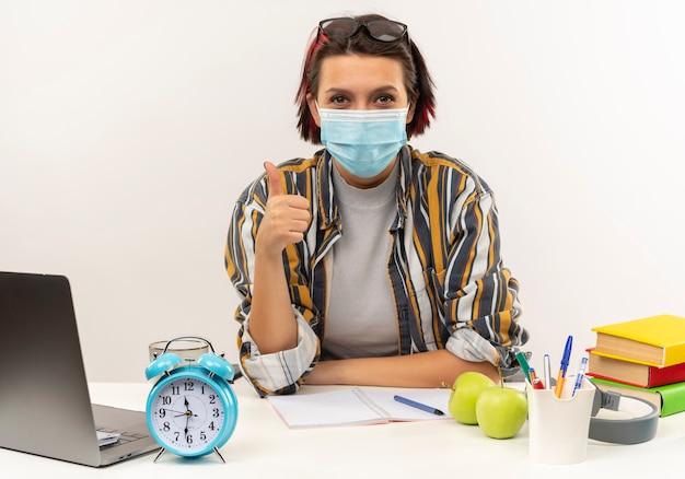 Zadowolona młoda studentka w okularach na głowie i masce siedzi przy biurku pokazując kciuk do góry na białym tle na białej ścianie