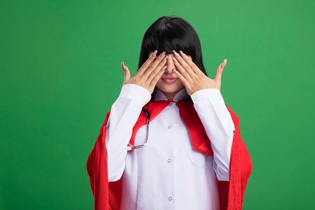 Zadowolona młoda superbohaterka ubrana w stetoskop w szlafroku i pelerynie zakryte oczy z rękami odizolowanymi na zielonej ścianie