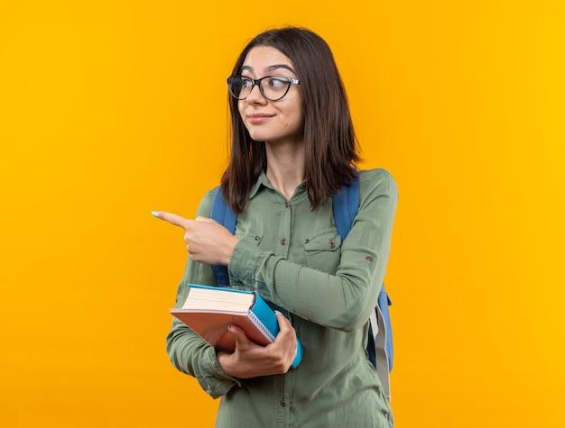 Zadowolona młoda szkolna kobieta nosząca plecak z okularami trzymająca książki wskazuje z boku