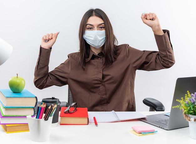 Zadowolona młoda szkolna kobieta w masce medycznej siedzi przy stole ze szkolnymi narzędziami pokazującymi gest tak!