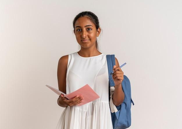 Zadowolona młoda uczennica na sobie tylną torbę, trzymając notatnik i długopis na białym tle