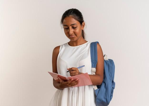 Zadowolona młoda uczennica nosząca torbę z tyłu trzymając i napisz coś na notatniku na białym tle