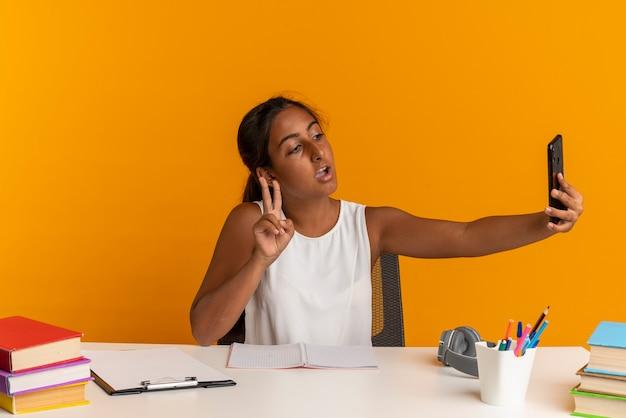 Zadowolona Młoda Uczennica Siedząca Przy Biurku Ze Szkolnymi Narzędziami Robi Selfie I Pokazuje Gest Pokoju Na Pomarańczowej ścianie Darmowe Zdjęcia