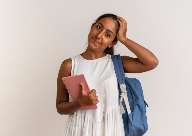 Zadowolona młoda uczennica ubrana w tylną torbę, trzymając notebook i kładąc rękę na głowie na białym tle