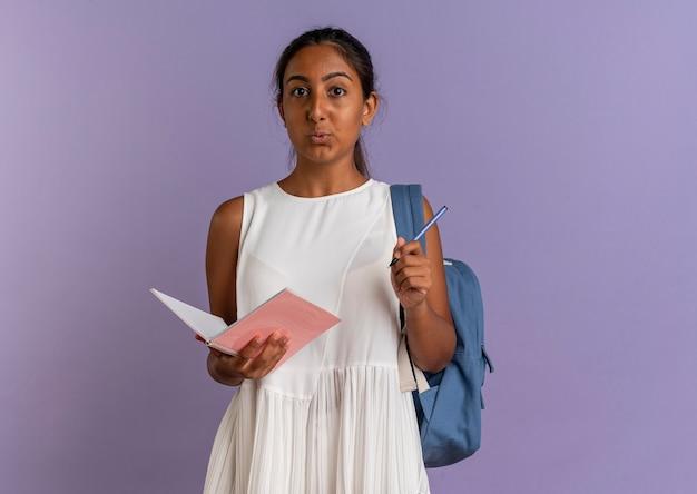 Zadowolona młoda uczennica ubrana w tylną torbę, trzymając notes i długopis na fioletowo