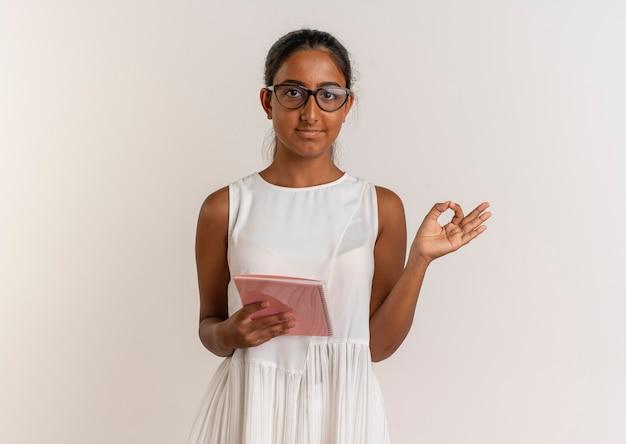 Zadowolona młoda uczennica w okularach trzyma notes i pokazuje gest okey na białej ścianie