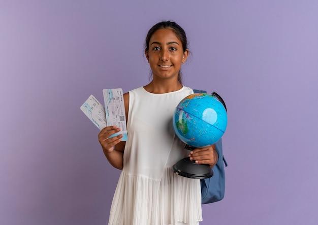 Zadowolona młoda uczennica w torbie z biletami i kulą ziemską na fioletowo
