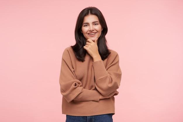 Zadowolona młoda urocza brązowowłosa kobieta z luźnymi włosami trzymająca brodę z uniesioną ręką i radośnie patrząca z przodu z ładnym uśmiechem, odizolowana na różowej ścianie