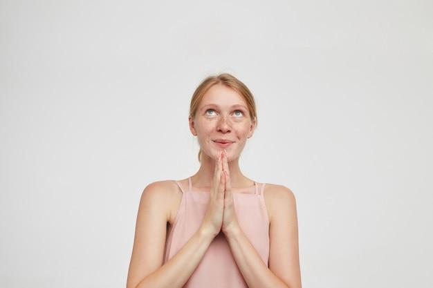 Zadowolona młoda urocza rudowłosa dama z naturalnym makijażem, wyglądająca marzycielsko w górę, z czarującym uśmiechem i składanymi dłońmi, stojąca na białym tle