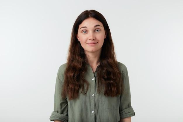 Zadowolona młoda zielonooka ładna brunetka z naturalnym makijażem
