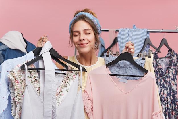 Zadowolona modelka z przyjemnością zamykająca oczy, stojąc w szatni, trzymając wiele wieszaków z ubraniami, chcąc kupić wszystko