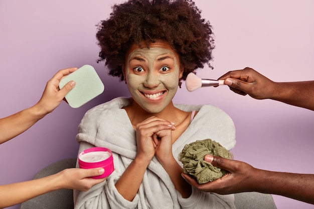 Zadowolona modelka z radością patrzy w obiektyw, trzyma dłonie razem i gryzie usta, nakłada glinkową maseczkę dla zdrowej, świeżej skóry