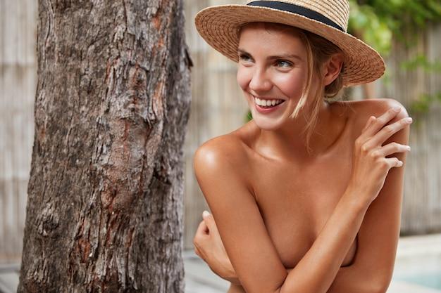 Zadowolona naga kobieta chowa piersi, radośnie odwraca wzrok, nosi słomkowe letnie kapelusze, ma przyjemny szeroki uśmiech na twarzy. naga suka ma zadbaną skórę