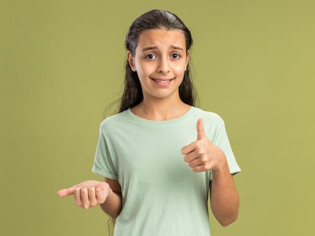Zadowolona nastolatka patrząca na przód pokazujący pustą rękę i kciuk na białym tle na oliwkowozielonej ścianie