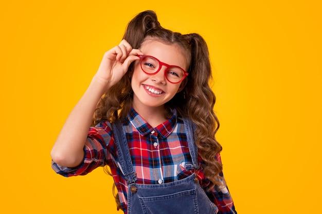 Zadowolona nastolatka w kraciastej koszuli i kombinezonie dżinsowym dotykająca modnych okularów i wyglądająca