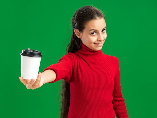 Zadowolona nastolatka wyciąga plastikową filiżankę kawy w kierunku kamery patrząc na przód na zielonej ścianie