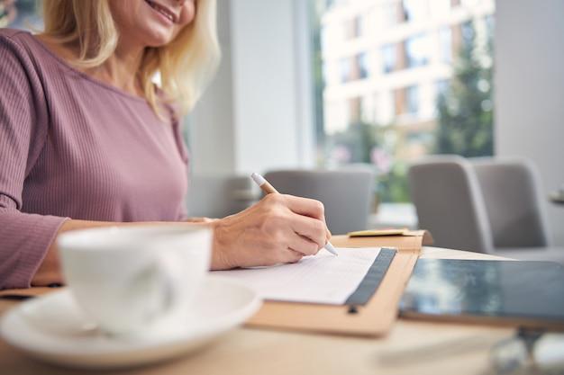 Zadowolona osoba płci żeńskiej zachowująca uśmiech na twarzy podczas pisania biznesplanu na kartce papieru