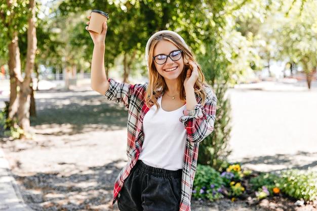 Zadowolona pani w modnych okularach, trzymając filiżankę kawy i śmiejąc się. zewnątrz portret pięknej dziewczyny europejskiej spaceru w parku.
