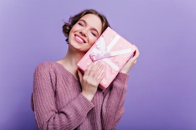 Zadowolona pani z efektownym makijażem pozuje z prezentem noworocznym na fioletowej ścianie. marzycielska krótkowłosa dziewczyna stojąca z zamkniętymi oczami, trzymająca prezent urodzinowy.