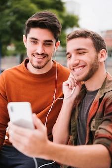 Zadowolona para gejów w słuchawkach słuchających muzyki na telefonie komórkowym