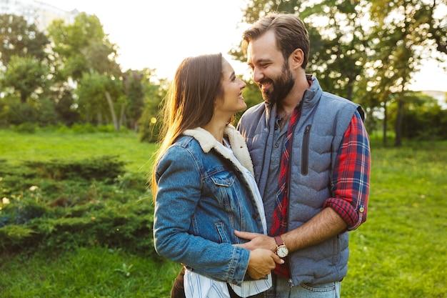Zadowolona para mężczyzna i kobieta ubrani w codzienny strój przytulający się i patrzący na siebie podczas wspólnego spaceru po zielonym parku
