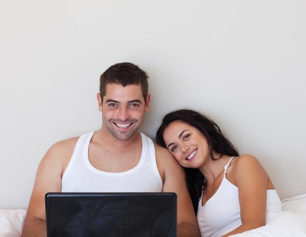 Zadowolona para siedzi na łóżku z laptopem
