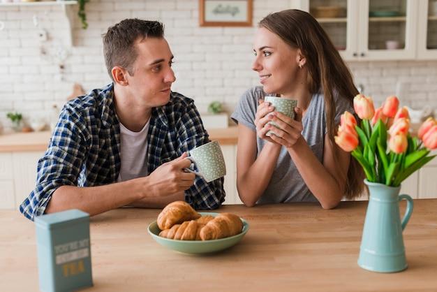 Zadowolona para siedzi przy stole i cieszy się herbatę
