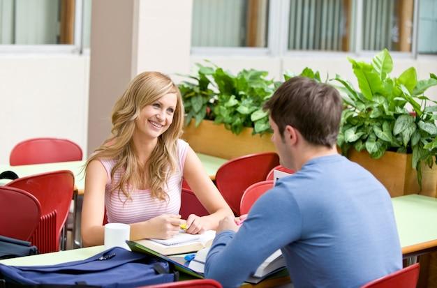 Zadowolona para studentów pracujących razem w stołówce