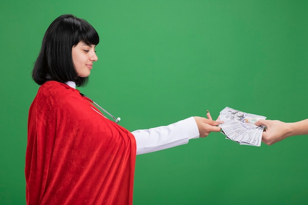 Zadowolona, patrząc na bok młoda dziewczyna superbohatera w stetoskopie z szlafrokiem medycznym i płaszczem kogoś, kto daje jej pieniądze na zielono