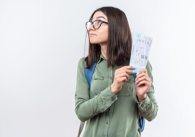 Zadowolona, patrząc na młodą szkołę w okularach z plecakiem, trzymającą bilety