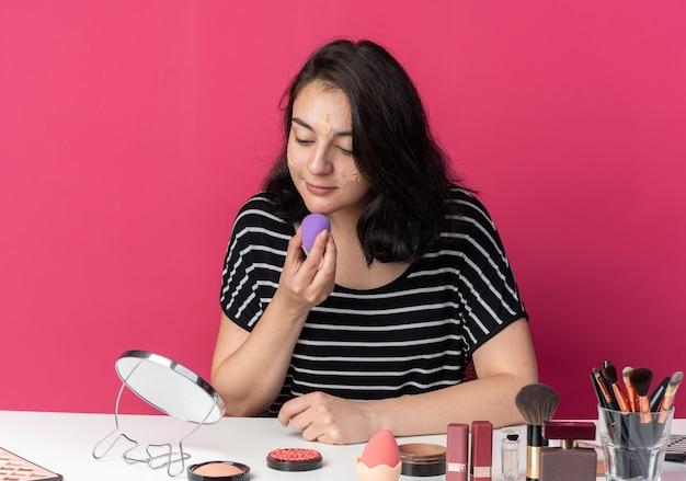 Zadowolona patrząc w lustro młoda piękna dziewczyna siedzi przy stole z narzędziami do makijażu, nakładającymi krem tonujący z gąbką odizolowaną na różowej ścianie