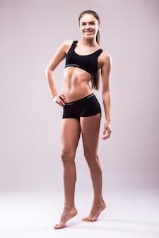 Zadowolona, pewna siebie, aktywna zdrowa kobieta w odzieży sportowej z rękami na biodrach