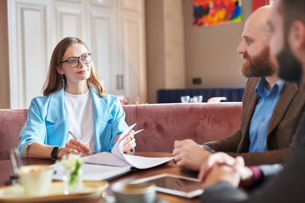 Zadowolona pewna siebie biznesowa dama w okularach siedzi przy stole w kawiarni i podpisuje umowę z nowymi dostawcami
