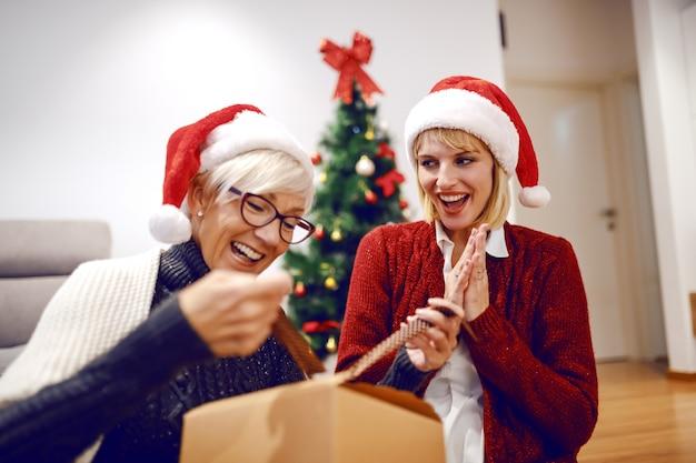 Zadowolona piękna blondynka kaukaska odpakowująca prezent świąteczny siedząc na podłodze w salonie. obok niej siedzi jej córka. obaj mają na głowach czapki mikołaja.