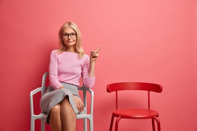 Zadowolona piękna dojrzała kobieta w eleganckim stroju siedzi samotnie na krześle i wskazuje na miejsce na kopię