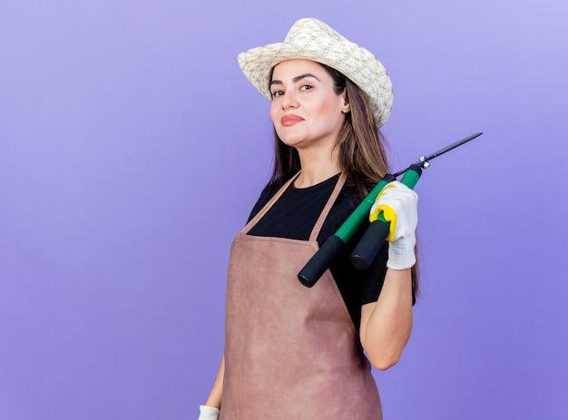 Zadowolona piękna dziewczyna ogrodnik w mundurze na sobie kapelusz ogrodniczy i rękawiczki stawiając maszynkę do strzyżenia na ramieniu na białym tle na niebieskim tle z miejsca na kopię