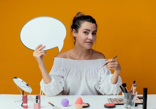 Zadowolona piękna dziewczyna siedzi przy stole z narzędziami do makijażu, trzyma bańkę czatu i pędzel do makijażu na pomarańczowej ścianie