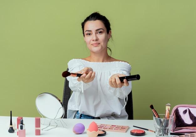 Zadowolona piękna dziewczyna siedzi przy stole z narzędziami do makijażu, trzyma pędzel do makijażu i tusz do rzęs, patrząc odizolowane na zielonej ścianie