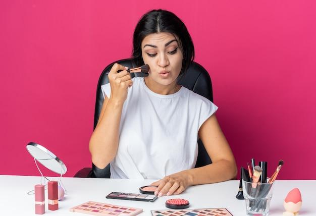 Zadowolona piękna kobieta siedzi przy stole z narzędziami do makijażu, nakładając pudrowy róż za pomocą pędzla