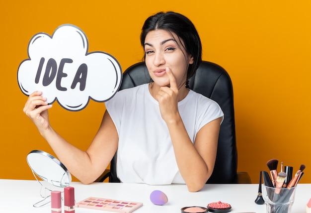 Zadowolona piękna kobieta siedzi przy stole z narzędziami do makijażu trzymając bańkę pomysłu