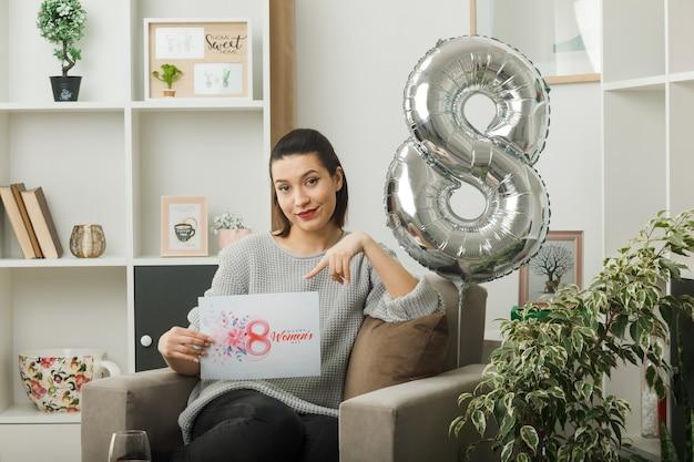 Zadowolona piękna kobieta w szczęśliwy dzień kobiet trzyma i wskazuje na pocztówkę, siedząc na fotelu w salonie