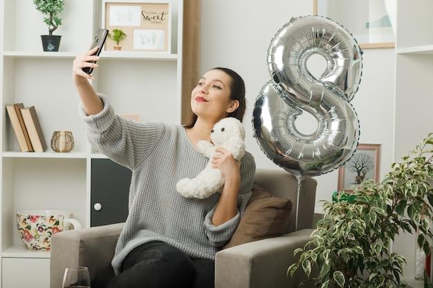 Zadowolona piękna kobieta w szczęśliwy dzień kobiet trzymająca misia robi selfie siedząc na fotelu w salonie