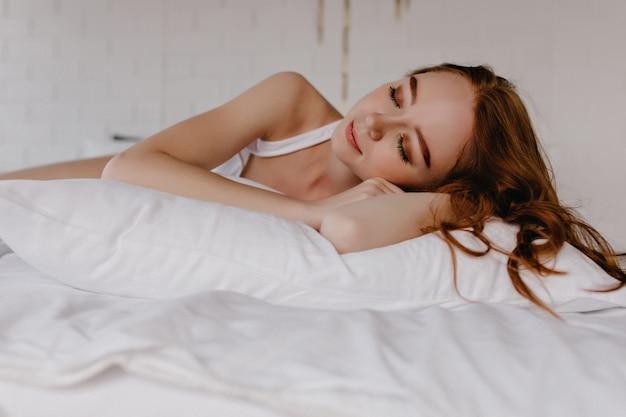 Zadowolona piękna kobieta z modnym makijażem śpi z uśmiechem. wewnątrz zdjęcie czarującej kręconej dziewczyny.