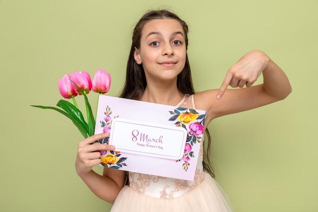 Zadowolona piękna mała dziewczynka na szczęśliwy dzień kobiet trzyma i wskazuje na kwiaty z kartką z życzeniami