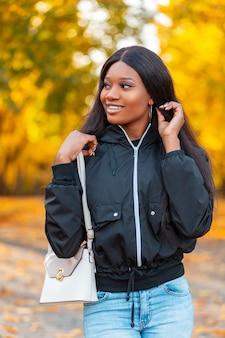 Zadowolona piękna młoda uśmiechnięta czarna kobieta w modnej kurtce z niebieskimi dżinsami i stylową torebką spaceruje w naturze na tle jasnożółtych jesiennych liści