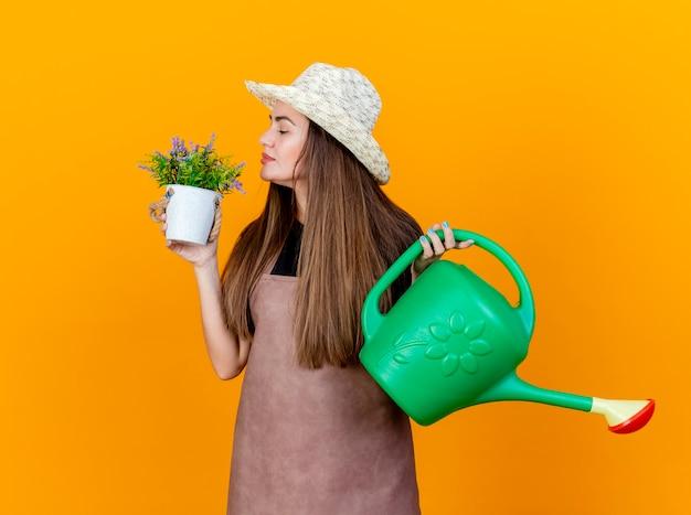 Zadowolona piękna ogrodniczka w mundurze i kapeluszu ogrodniczym trzyma konewkę i wącha kwiat w doniczce w dłoni na białym tle na pomarańczowym tle