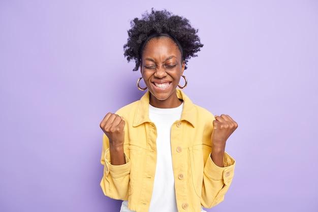 Zadowolona podekscytowana ciemnoskóra młoda kobieta podnosi zaciśnięte pięści i coś świętuje