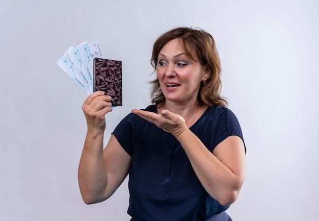 Zadowolona podróżniczka w średnim wieku trzyma i wskazuje biletami ręcznymi z portfelem na odizolowanej białej ścianie