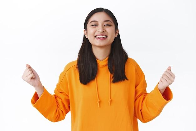 Zadowolona, pomyślna studentka z azji, zdała egzamin, wygrała loterię, pompowała pięścią i cieszyła się poczuciem osiągnięcia, świętowała wspaniałe wieści, triumfowała mówiąc tak, stojąca biała ściana