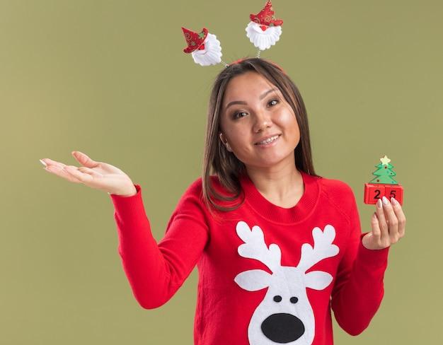 Zadowolona, przechylająca głowę młoda azjatycka dziewczyna ubrana w obręcz do włosów z bożonarodzeniowymi włosami, trzymająca świąteczne zabawki z rękami po bokach odizolowanych na oliwkowej ścianie